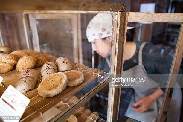 A woman stocking her bakery shelves