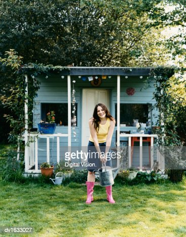 Woman Stood in Front of a Small Wooden Bungalow, Holding a Watering Can