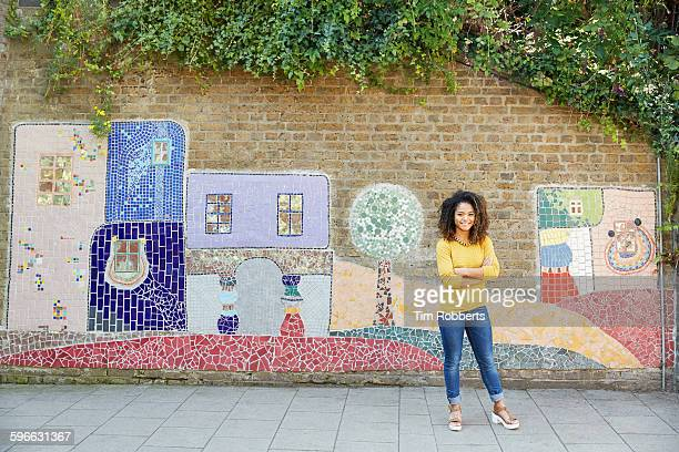 Woman stood in front of art wall.