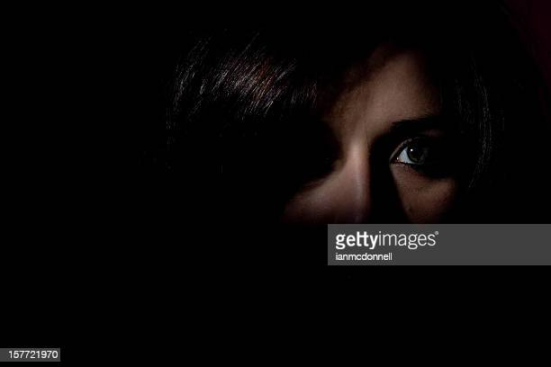 Woman stood in the dark showing half her face looking scared