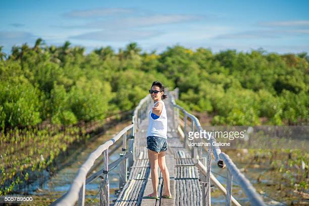 Woman stood on a bridge looking back over her shoulder