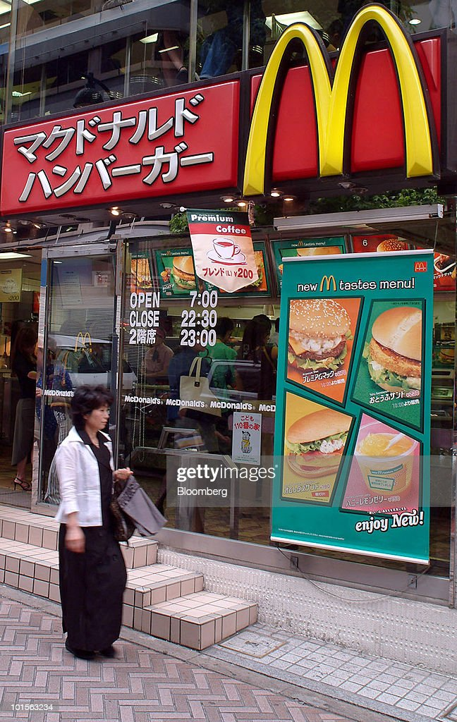 A woman stops to read the 'New Tastes Menu' advertisement outside a McDonald's restaurant in Shinjuku, Tokyo Monday, June 9, 2003. Japan, the biggest importer of U.S. beef, said it will ban imports of the meat and processed foods containing U.S. beef after a laboratory in the U.K. confirmed a cow from Washington state tested positive for mad cow disease. Photographer: Charles Pertwee/Bloomberg via Getty Images News