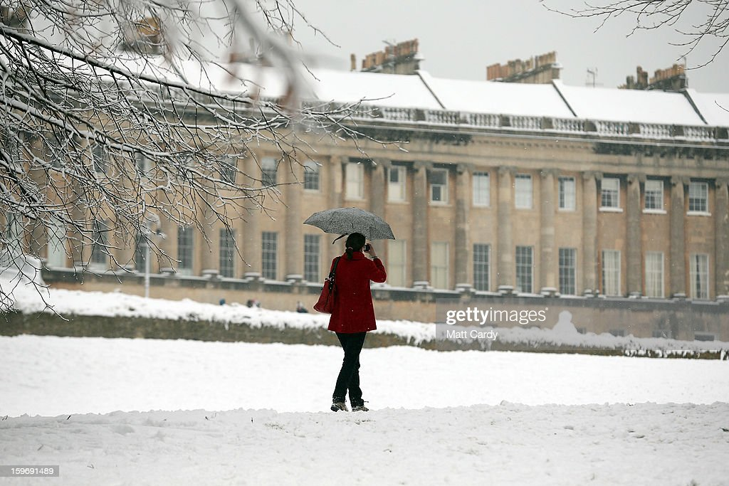 A woman stops to take a photograph of the front of the Royal Crescent overlooking Victoria Park on January 18, 2013 in Bath, England. Heavy snow is bringing widespread disruption to many parts of the UK.
