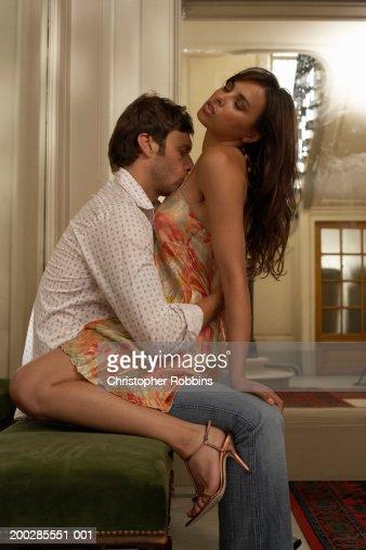 Woman straddling man sitting on foyer bench, man kissing woman's chest : Stock Photo