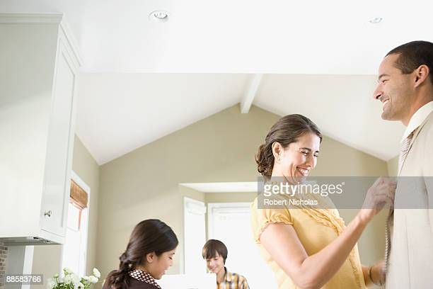 Woman straightening husbands tie at home