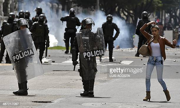 A woman straightens her hair as riot policemen stand in position during clashes within the first day of a national strike by farmers protesting...