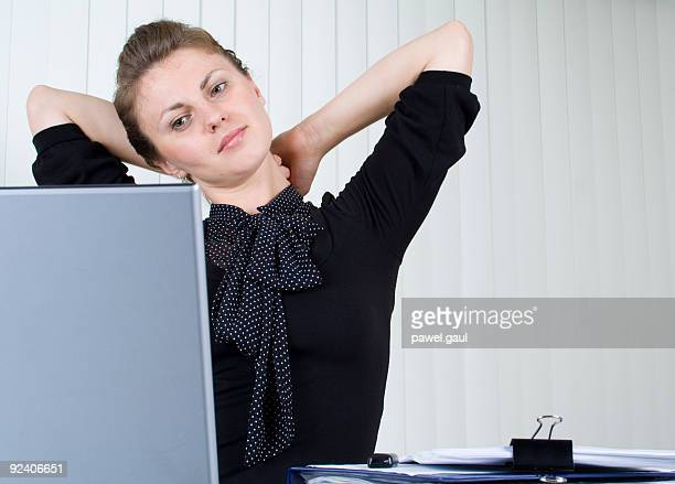 Woman streaching out behind computer