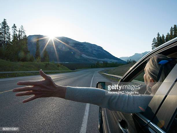 Woman stretches arm out of car window, mtn sunrise