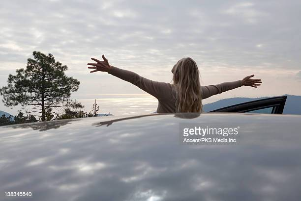 Woman stretches arms above car top, distant sea
