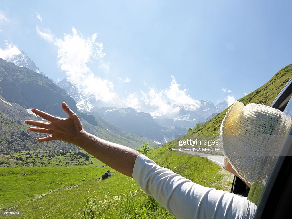 Woman stretches arms out of car window, mtn meadow : Stock Photo