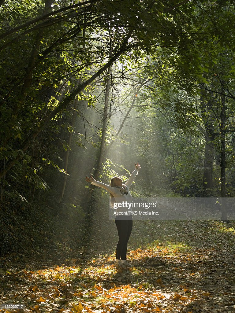 Woman stretches arms upwards into shaft of light : Stock Photo