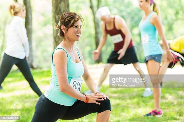 Mulher alongamentos antes de 5 K corrida