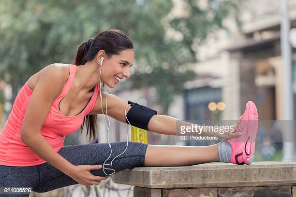 Woman stretches legs before morning run