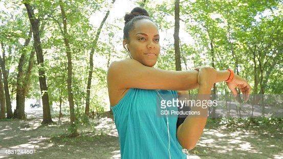 Mujer estiramiento armas antes de correr en camino durante el ejercicio