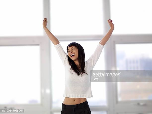 Woman stretching arms, eyes closed, laughing