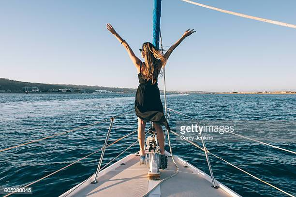 Woman stretching arms on sailboat, San Diego Bay, California, USA