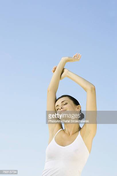 Woman stretching arms overhead, sky in background, low angle view