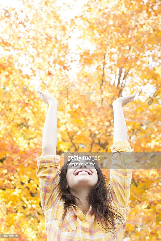 Woman stretching arms up in front of Autumn tree : Stock Photo