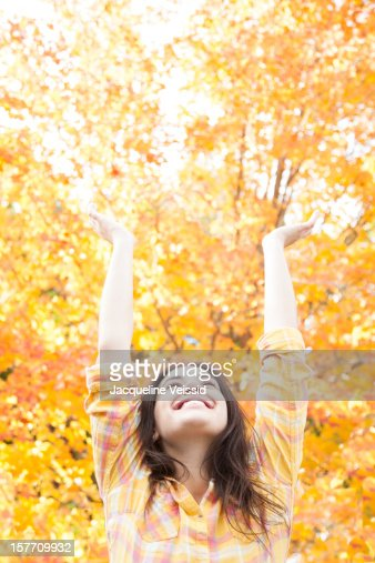 Woman stretching arms up in front of Autumn tree : Stockfoto