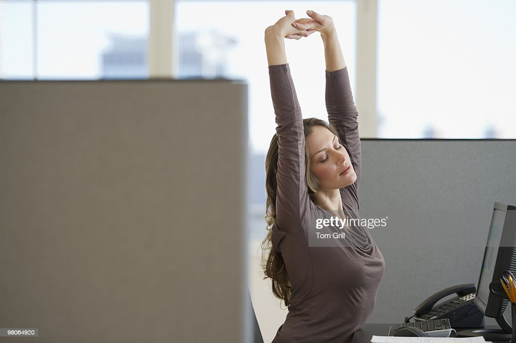 Woman stretching at her office desk : Stock Photo