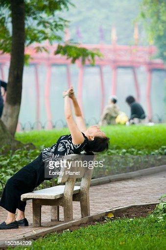 Woman stretching beside Hoan Kiem Lake. : Stock Photo