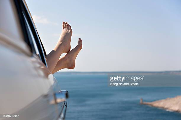 Woman stretching feet from car by sea