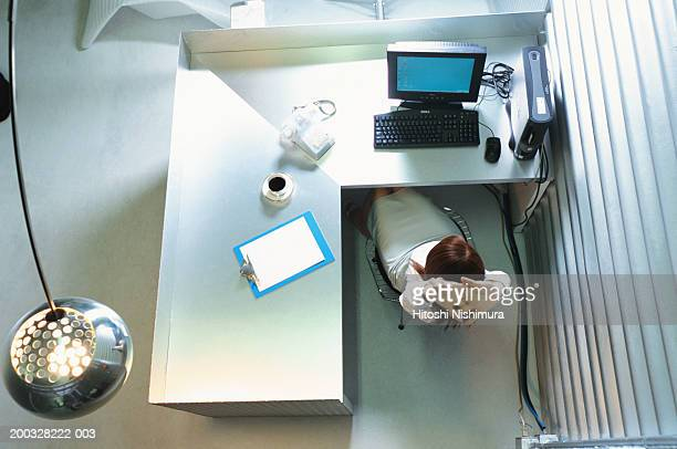 Woman stretching hands at office desk, elevated view