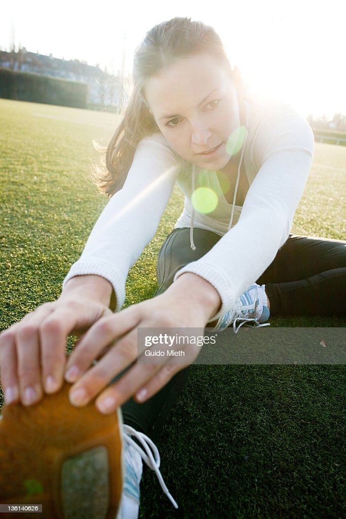 Woman stretching her leg on grass ground : Stock Photo