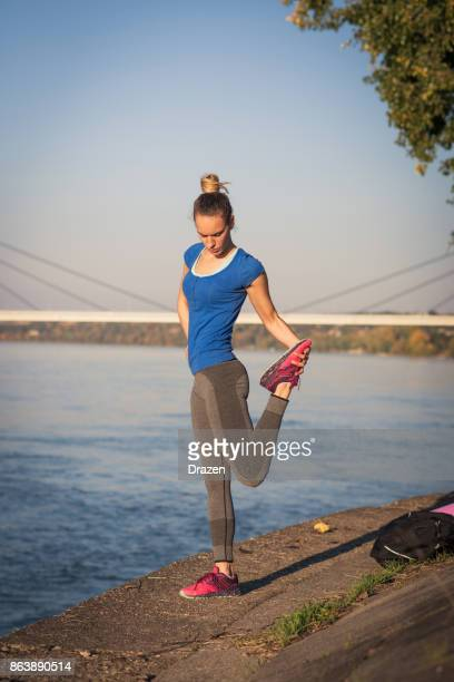Woman stretching her quadriceps muscles after jogging
