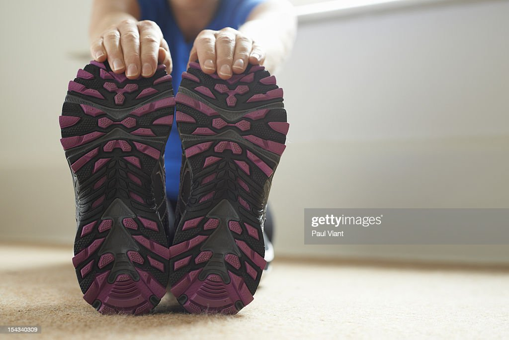 Woman stretching, holding her running shoes