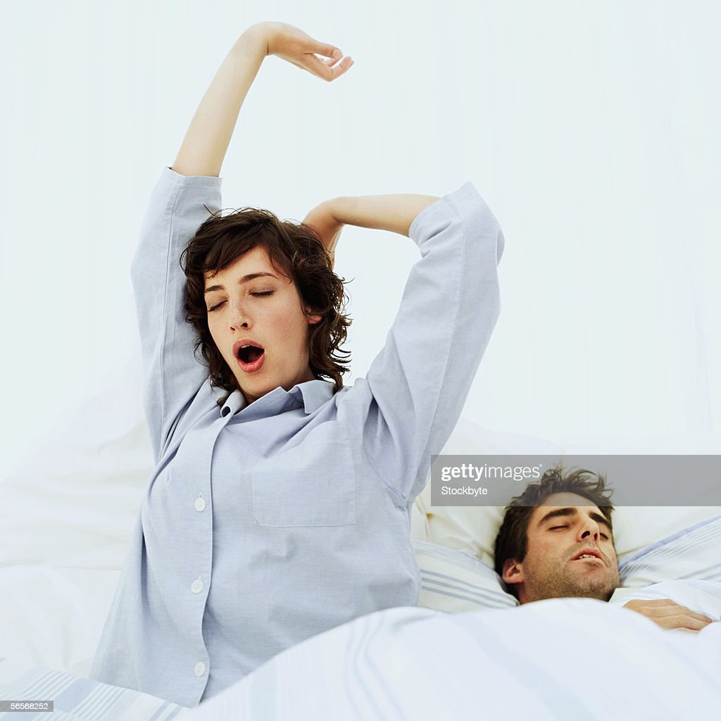 woman stretching in bed with a man sleeping beside her : Stock Photo
