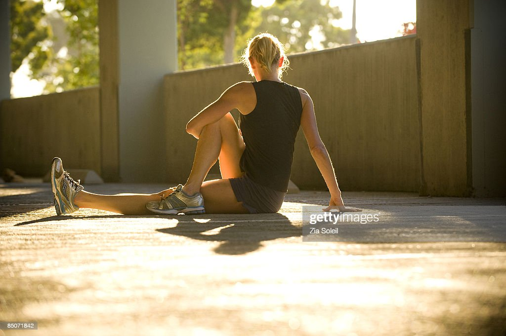woman stretching in morning light in parking garag : Stock Photo