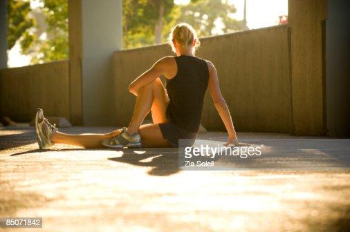 woman stretching in morning light in parking garag : Stockfoto