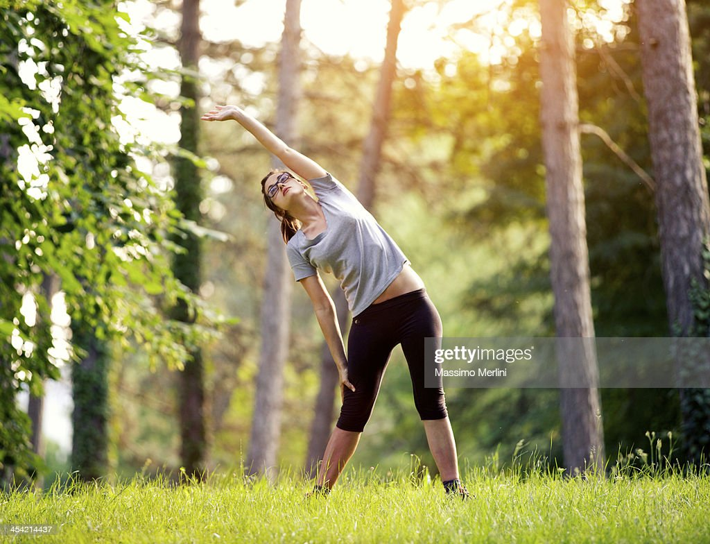 Woman stretching in the woods