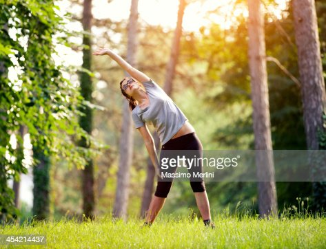 Woman stretching in the woods : Stock Photo