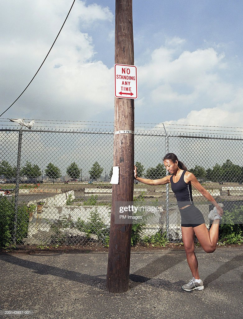 Woman stretching, leaning against utility pole
