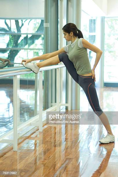 Woman stretching leg on barre