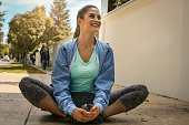 Woman stretching leg on urban sidewalk. Young woman exercise.'n