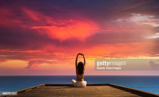 Woman stretching on a dock at sunset
