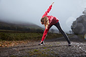 Woman stretching on dirt road