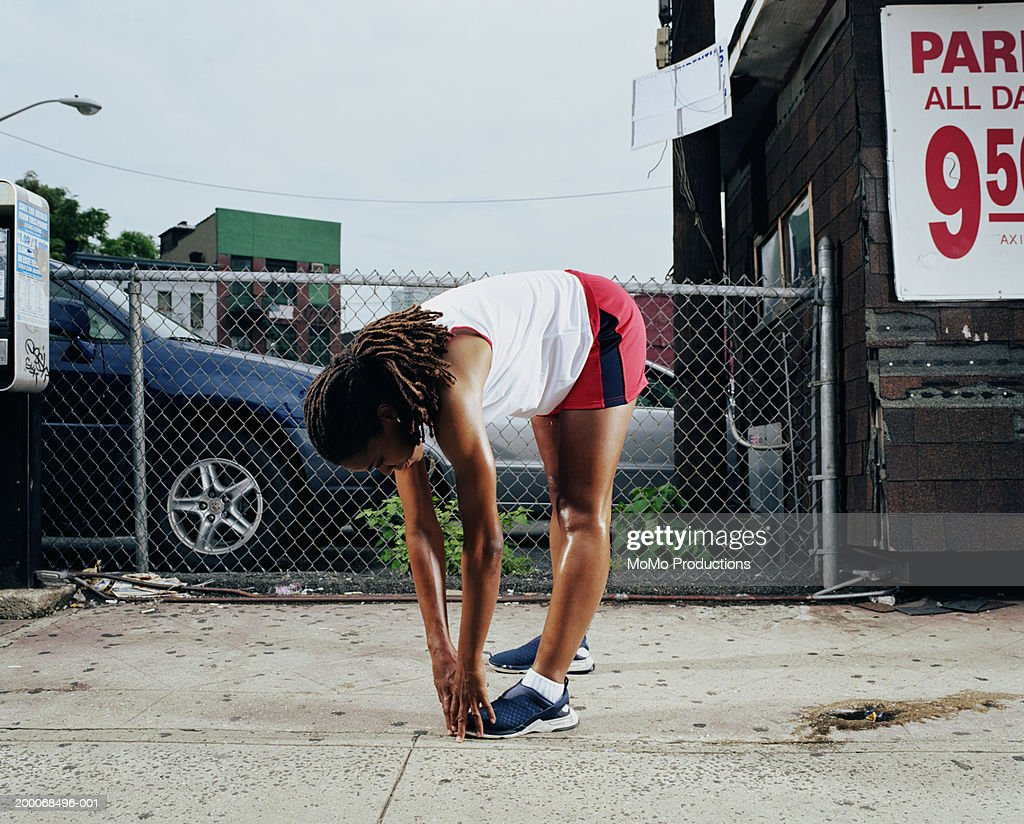 Woman stretching on sidewalk : Stock Photo