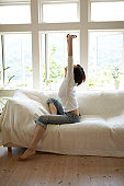 Woman stretching on sofa in living room