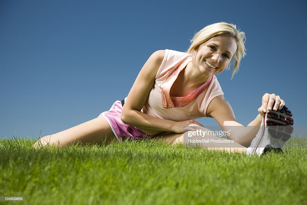 woman stretching on the grass : Stock Photo