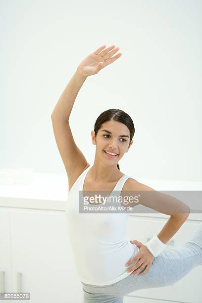 Woman stretching, one arm raised