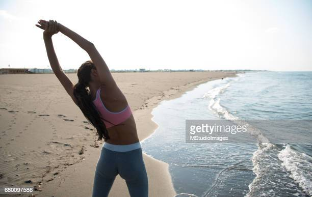 Woman stretching out at the beach.