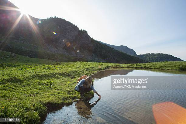 Woman strokes surface of mountain pond, sunrise