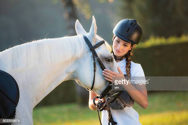 Woman stroking a horse on the head in nature