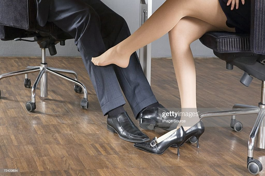 Woman stroking businessman's leg with her foot : Stock Photo