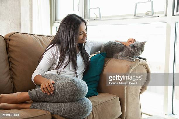Woman stroking cat on couch