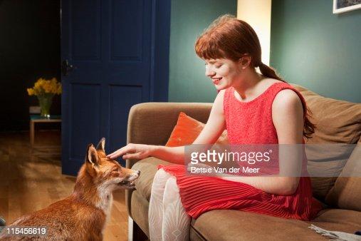 Woman stroking fox, while sitting on sofa.